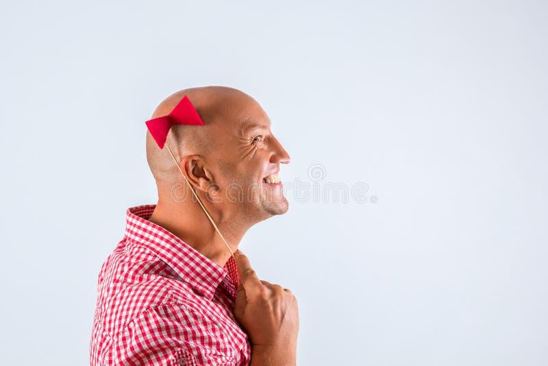 Härlig skallig positiv man som bort ser med en pilbåge på hans huvud, ett ställe för att skriva, vit bakgrund arkivfoto
