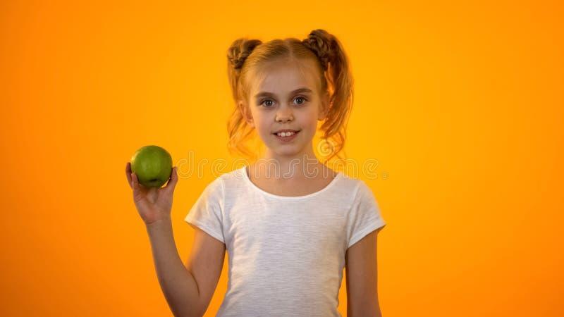 Härlig skolflicka som rymmer det nya gröna äpplet, sund näring, organisk mat arkivfoto