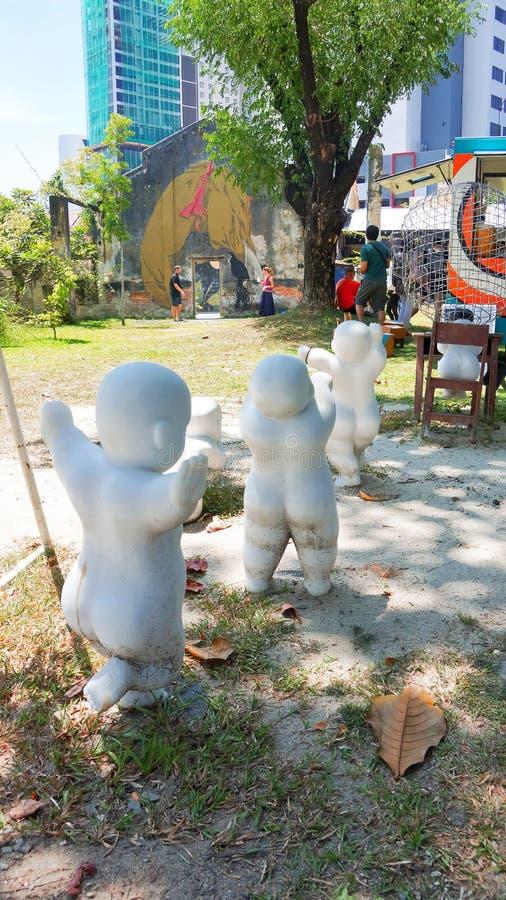 Härlig skulpturkonst av ungar som kör i Penang royaltyfri bild
