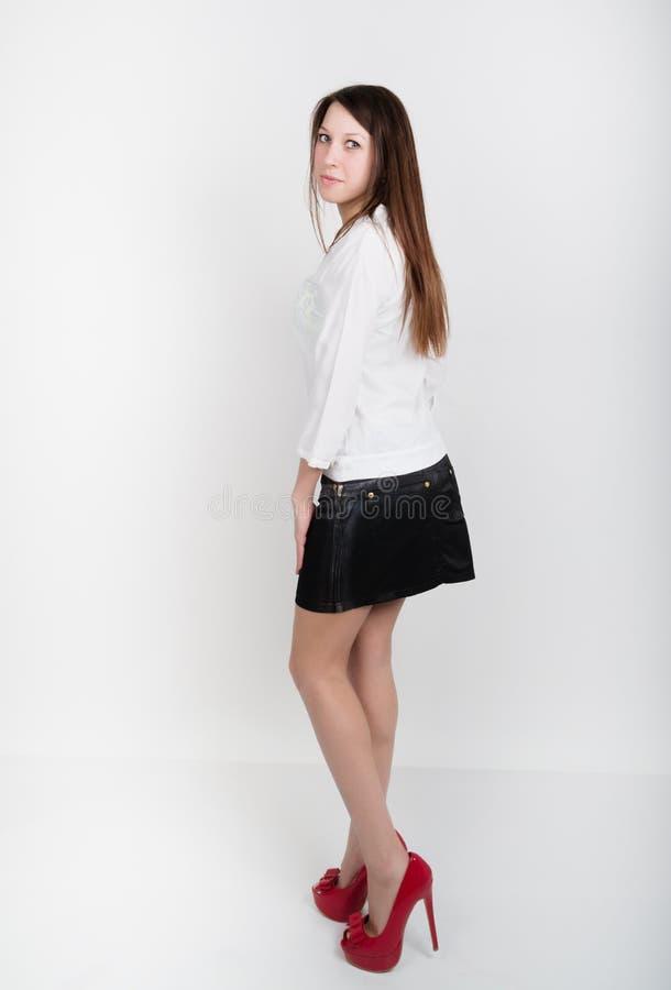 Härlig slank flicka i en kort svart kjol, en vit blus och röda skor med höga häl som poserar royaltyfri foto