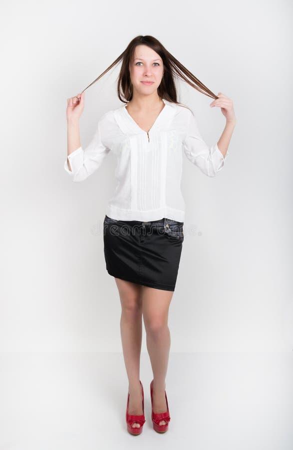 Härlig slank flicka i en kort svart kjol, en vit blus och röda skor med höga häl som rymmer hans hår royaltyfria foton