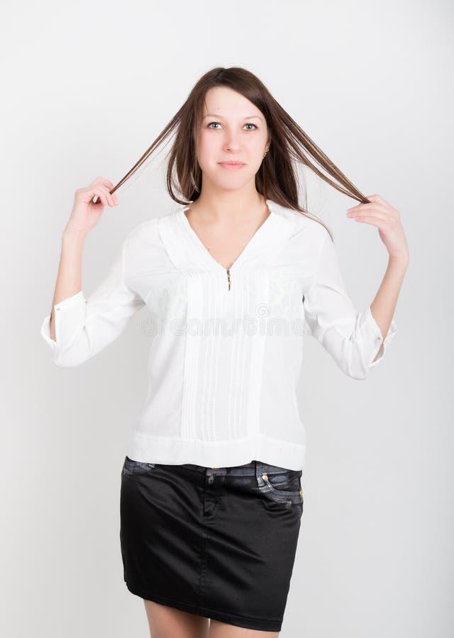 Härlig slank flicka i en kort svart kjol och vitblus som rymmer hans hår arkivfoton