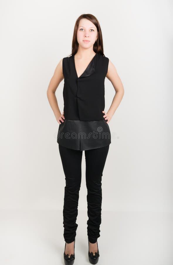 Härlig slank flicka i svartflåsanden och en svart sleeveless blus arkivbild