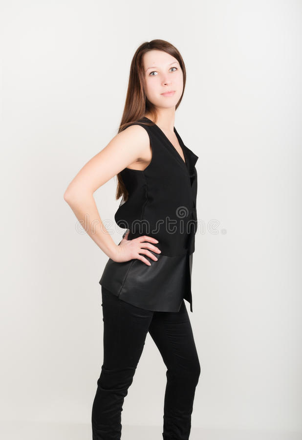 Härlig slank flicka i svartflåsanden och en svart sleeveless blus arkivbilder