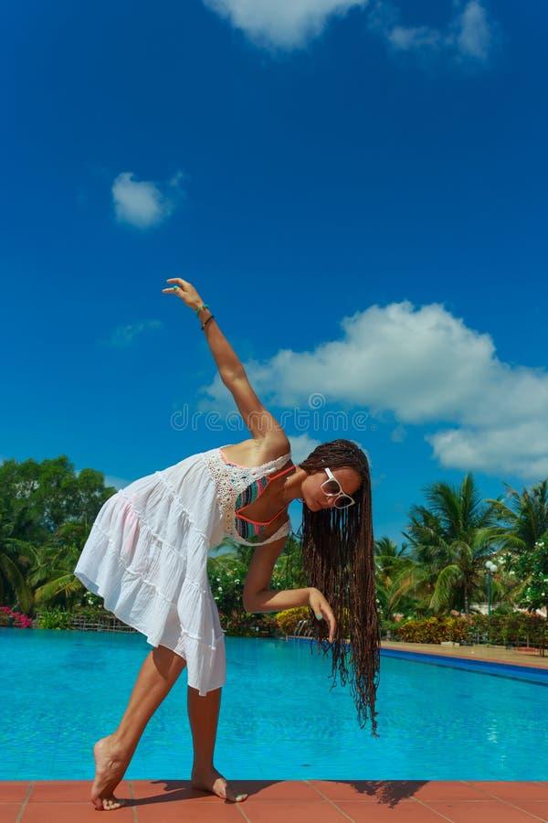 Härlig slank flicka som har gyckel nära det varma blåa vattnet med palmträd på bakgrund royaltyfria bilder
