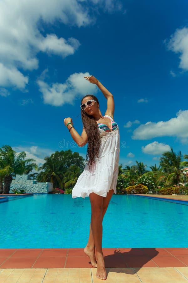 Härlig slank flicka som har gyckel nära det varma blåa vattnet med palmträd på bakgrund arkivfoton