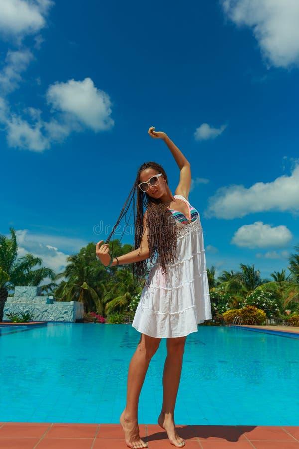 Härlig slank flicka som har gyckel nära det varma blåa vattnet med palmträd på bakgrund royaltyfri foto