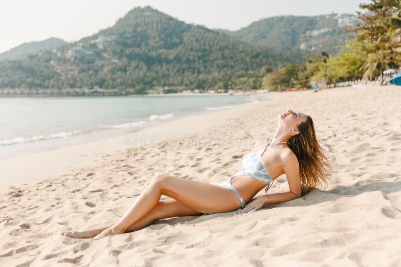 härlig slank flicka som vilar på den sandiga stranden arkivbilder