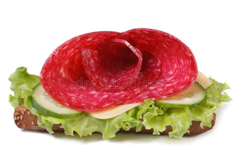 Härlig smörgås med isolerade salami, ost och grönsallat royaltyfri fotografi