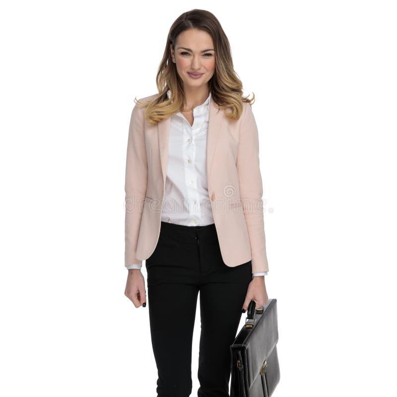 Härlig smart tillfällig kvinna som bär den rosa dräkten och rymmer portföljen arkivbild