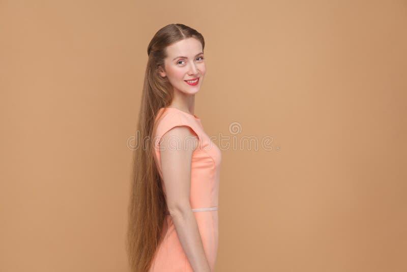 Härlig smileykvinna med långt brunt hår som ser kameran arkivfoto