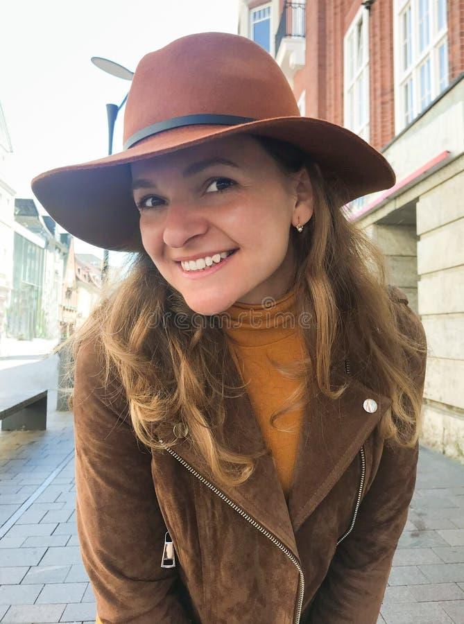 Härlig smilling kvinna i den bruna hatten som ser kameran royaltyfri fotografi