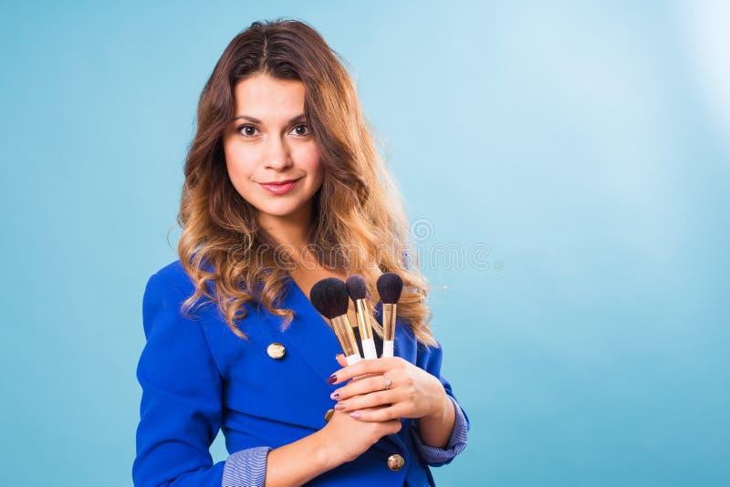 Härlig sminkkonstnär med borstar på blå bakgrund royaltyfria foton