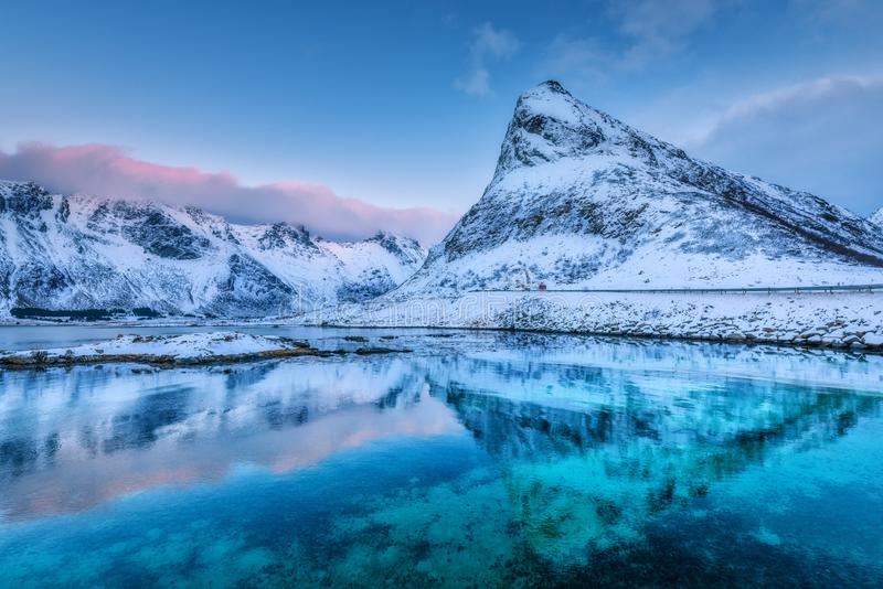 Härlig snö täckte berg och blå himmel reflekterade i vatten fotografering för bildbyråer