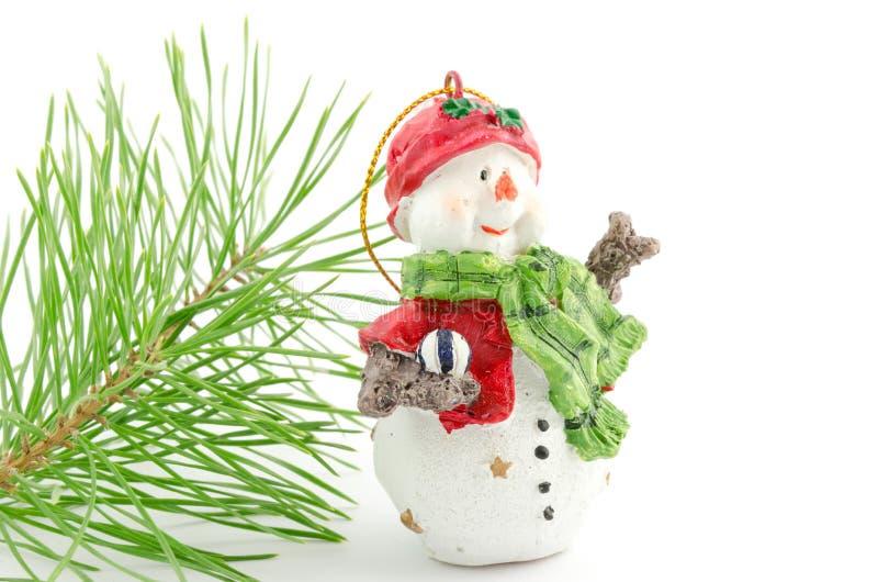Härlig snögubbe nära den isolerade filialen av julträdet royaltyfria foton