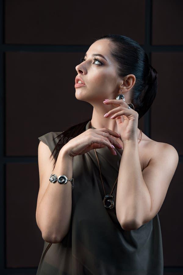 Härlig sofistikerad mörk haired kvinna som bär elegant pråligt fotografering för bildbyråer