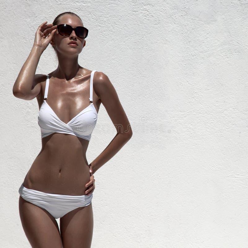 Härlig solbränd kvinnlig modell som poserar i bikini och solglasögon arkivfoto