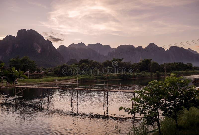 Härlig solnedgång över bergen, som dominerar Vang Vieng som förbiser den Nam Song floden och träbron, Laos arkivbilder