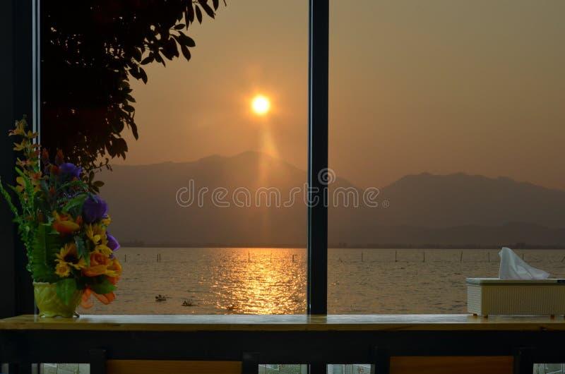 Härlig solnedgång över berget och sjön i fönstersikten royaltyfri foto