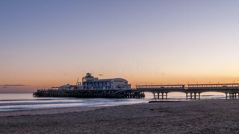 Härlig solnedgång över den härliga pir och den sandiga stranden av Bournemouth, England royaltyfria bilder