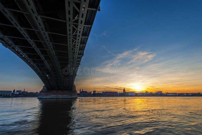 Härlig solnedgång över den Rhen-/Rhein floden och den gamla bron i strömförsörjning royaltyfria foton