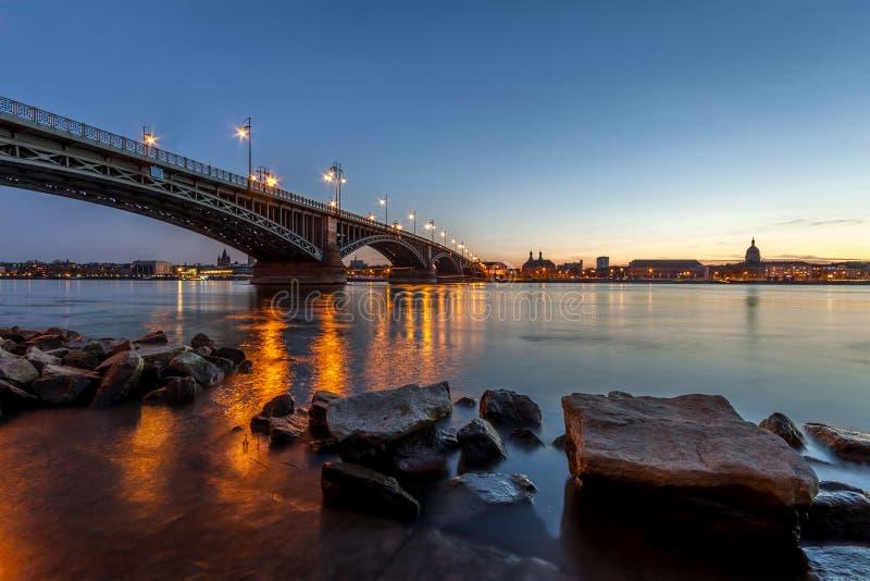 Härlig solnedgång över den Rhen-/Rhein floden och den gamla bron i strömförsörjning royaltyfri foto