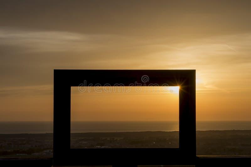 Härlig solnedgång över havet som inramas av en stor svart ram royaltyfri fotografi