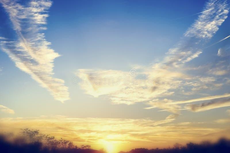 Härlig solnedgång- eller gryninghimmelbakgrund med att förbluffa moln och solsken som är utomhus- arkivbild