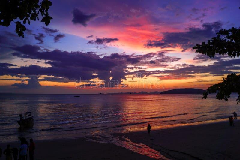 Härlig solnedgång med röda, purpurfärgade och gula färger på stranden i Thailand arkivfoton