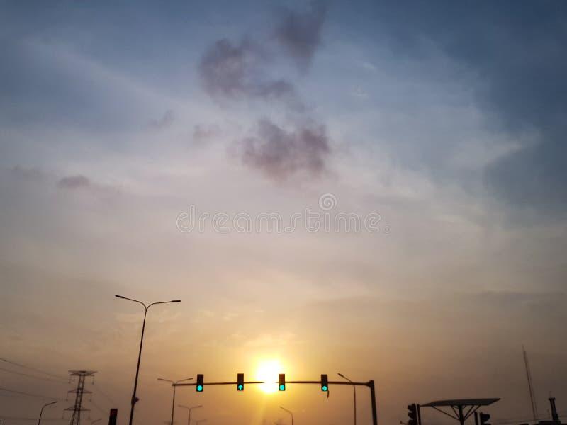 Härlig solnedgång med trafikljus som visar klarteckensignaler arkivfoton