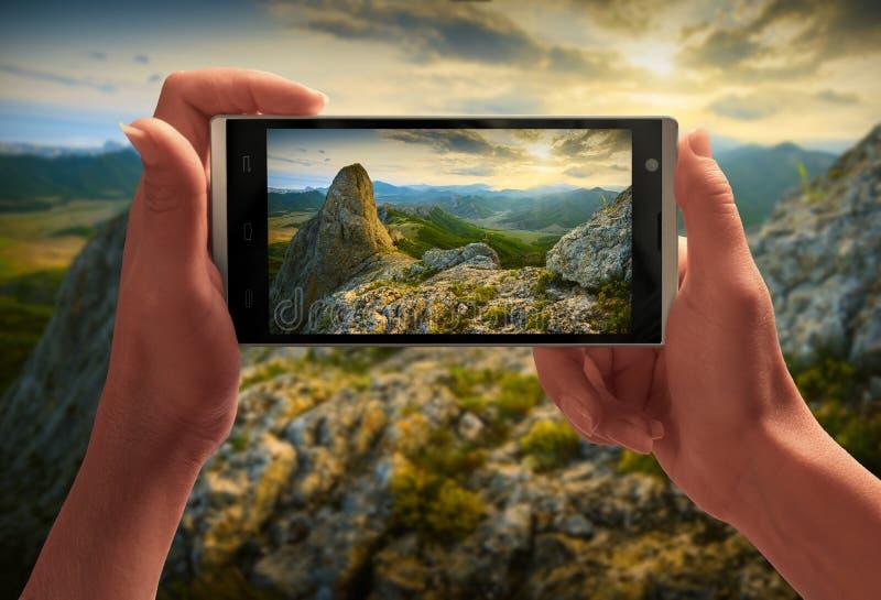 Härlig solnedgång ovanför bergdalen på en skärm av smartp royaltyfria foton
