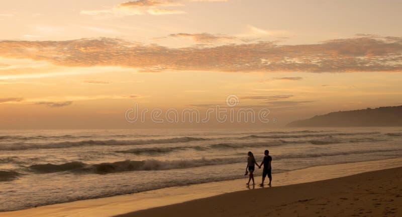 Härlig solnedgång på den Karon stranden Bränningen dunkar kusten Dunkla konturer för mörker av en man och en kvinna som går armen arkivbilder