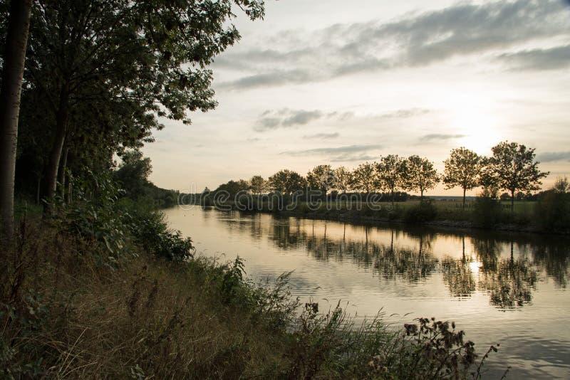 Härlig solnedgång på flodleien på kortrijk Belgien med träd som reflekterar i vattnet royaltyfria foton