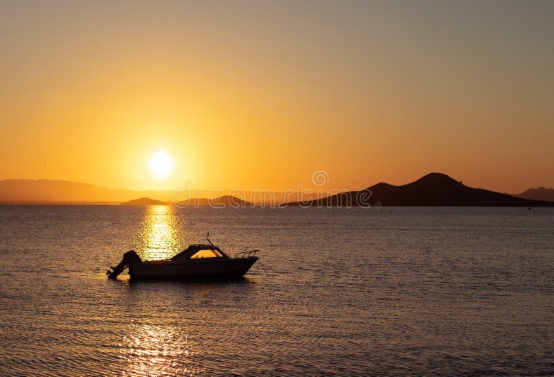 H?rlig solnedg?ng p? havet med konturn av ett fartyg och berg i bakgrunden Semesterplats i Mars Menor, Murcia, arkivfoton