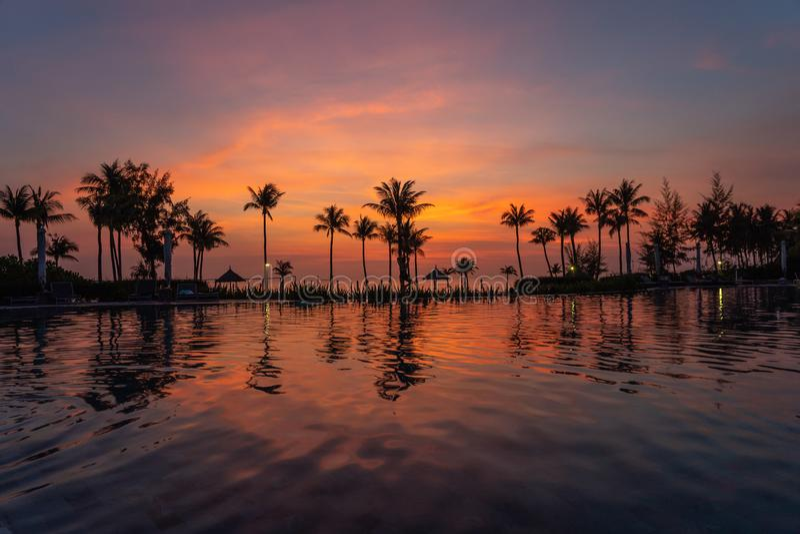 Härlig solnedgång på simbassängen i lyxig semesterort arkivbild