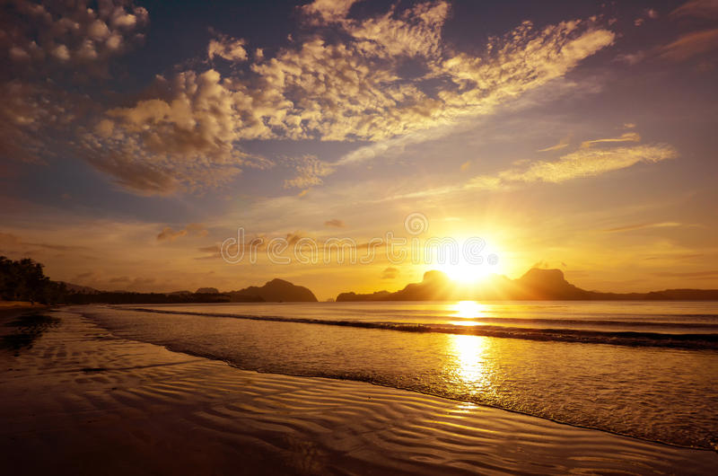 Härlig solnedgång på stranden under öarna med inställningen royaltyfria bilder