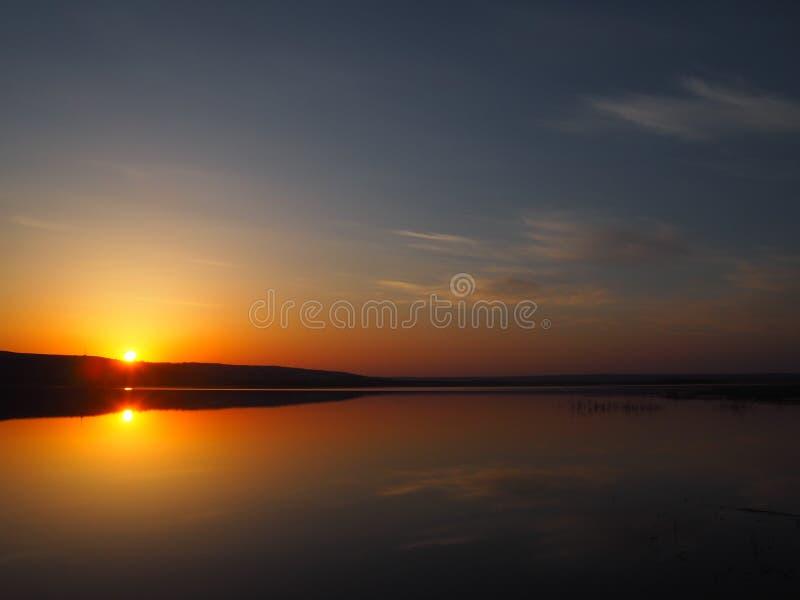 Härlig solnedgång under den lugna sjön arkivbild