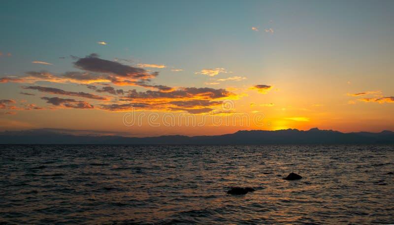 Härlig solnedgång vid havet Orange himmel och avlägset ölandskap Romantisk aftonseascape med solnedgång arkivbild