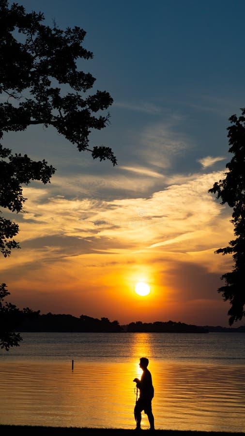 Härlig solnedgång vid sjön med en pojke som går hans hundkontur arkivbild