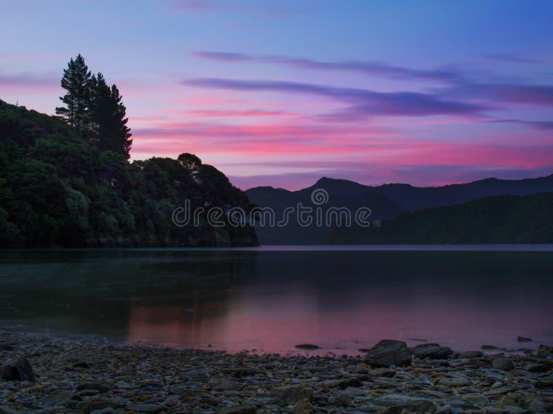 Härlig solnedgångaftonrodnad som reflekterar på det Kenepuru ljudet, Nya Zeeland arkivbild