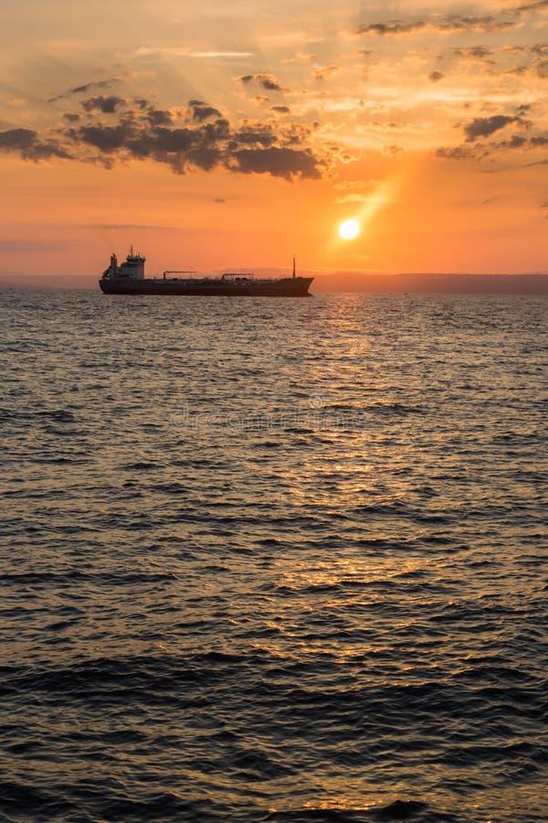 Härlig solnedgångsikt över havs- och skeppkonturn arkivfoton