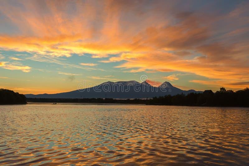 Härlig soluppgång över den volcanoesKluchevskaya gruppen med reflexion i floden Kamchatka fotografering för bildbyråer