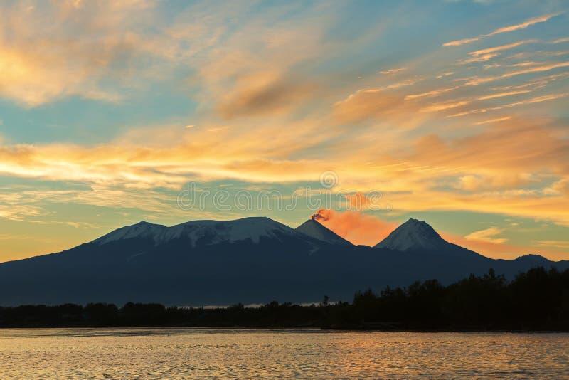 Härlig soluppgång över den volcanoesKluchevskaya gruppen med reflexion i floden Kamchatka royaltyfria bilder