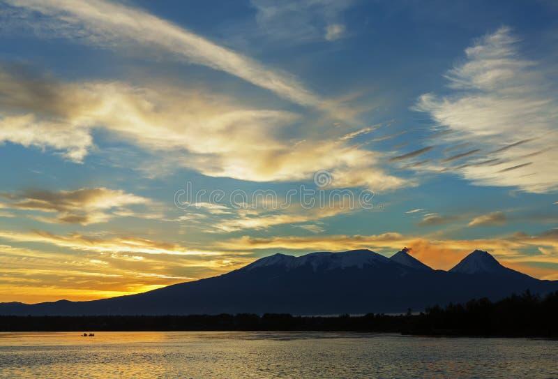 Härlig soluppgång över den volcanoesKluchevskaya gruppen med reflexion i floden Kamchatka royaltyfri foto