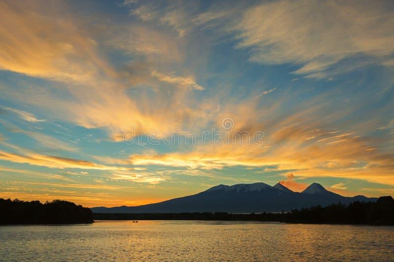 Härlig soluppgång över den volcanoesKluchevskaya gruppen med reflexion i floden Kamchatka arkivfoto