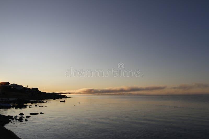 Härlig soluppgång över en arktisk sjö med dimma på horisonten royaltyfri bild