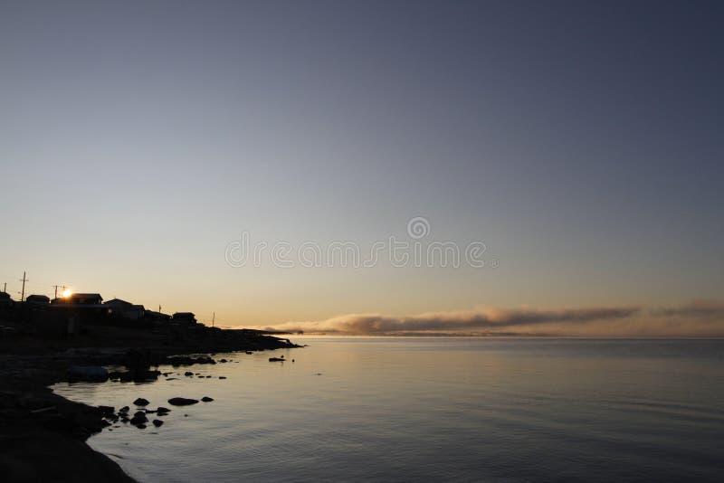 Härlig soluppgång över en arktisk sjö med dimma på horisonten och solen som når en höjdpunkt över byggnader arkivbild