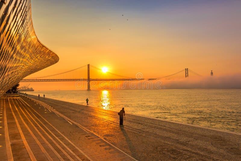 Härlig soluppgång i Lissabon, Portugal Sikt av 25 de Abril Bridge royaltyfri fotografi