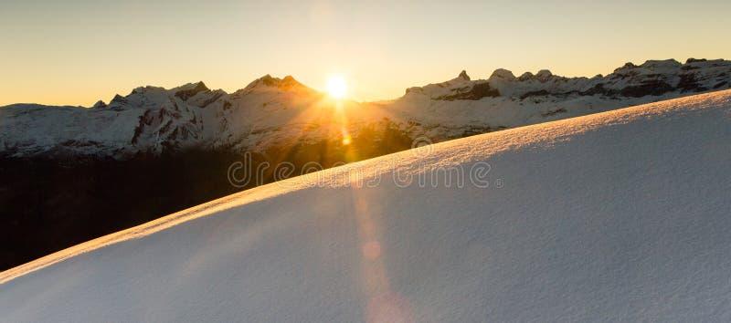 Härlig soluppgång i snöig berglandskap Upplysande ofördärvad pulversnö för solstrålar alps switzerland royaltyfria bilder