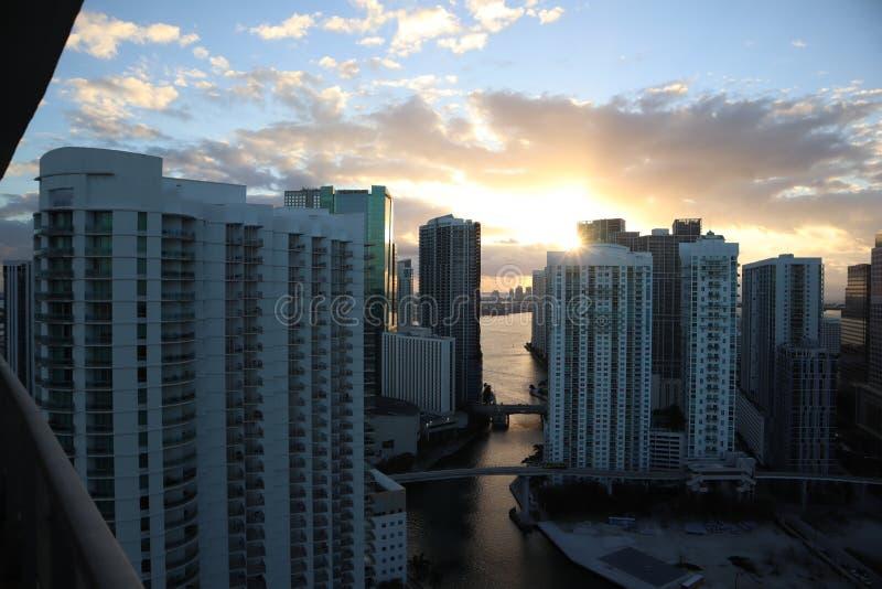 Härlig soluppgång i i stadens centrum miami solen bryter till och med molnen och skyskraporna sikt från det 38th golvet arkivbilder